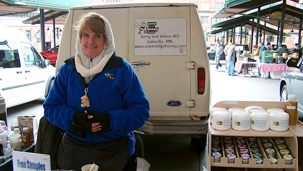 All bundled up in her coat, scarf, and gloves, Arlene Hill shows off her Aspen Ridge Honey and related products.