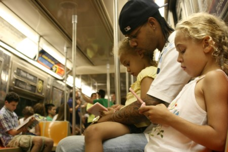 Two young girls and their father playing video games on public transit. Photo by Vincent.