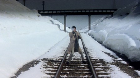 A man points a gun while standing on train tracks in a still from Tokyo Drifter