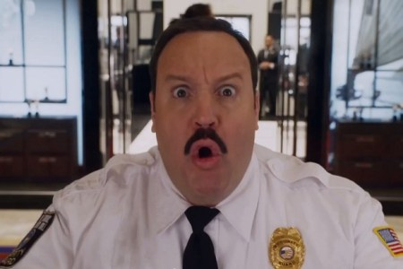 A mustached man in a security guard uniform looks surprised