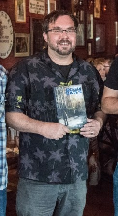 T. A. Wardrope holding his book, Arcadian Gates, and smiling