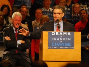 Bill Clinton looks on as Al Franken speaking at a podium labeled Obama + Fraken = Change
