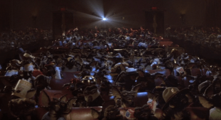 View of a movie theater from the screen shows the theater is full of gremlins. The light from the movie reel is on.