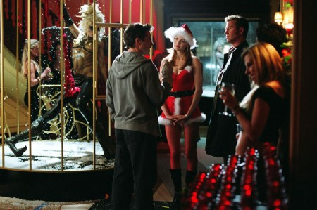 Harry tries to convince Harmony and Perry. It is clearly Christmastime—Harmony is wearing a skimpy Santa outfit with a hat. It appears they are at a stage or entertainment area, complete with someone in a cage.