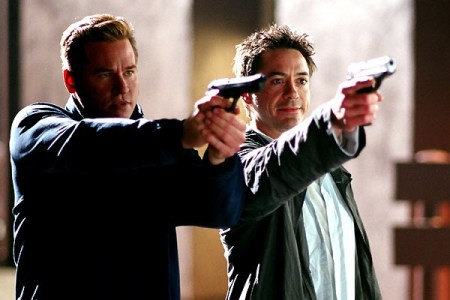 Perry and Harry get the drop on the bad guys. Both are aiming guns at the bad guys. Perry (Kilmer) is aiming with both hands and a serious face. Harry (Downey) is aiming one-handed and clearly is enjoying getting the drop on the bad guys.