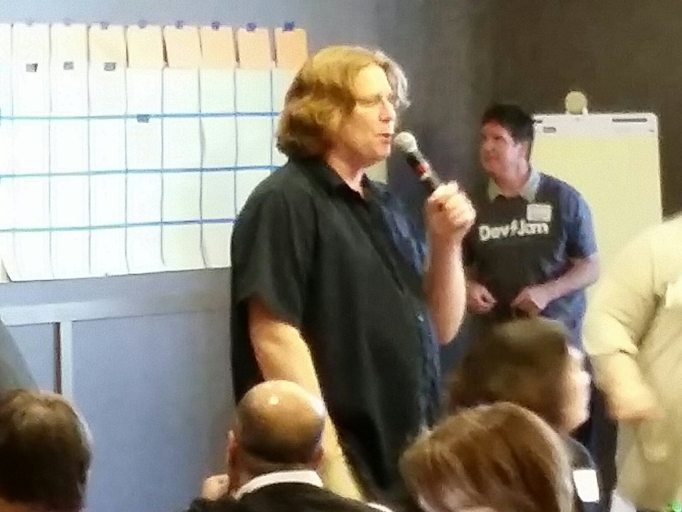 Cell phone photo of David holding a Microphone in front of a crowd at Agile Day November 2015