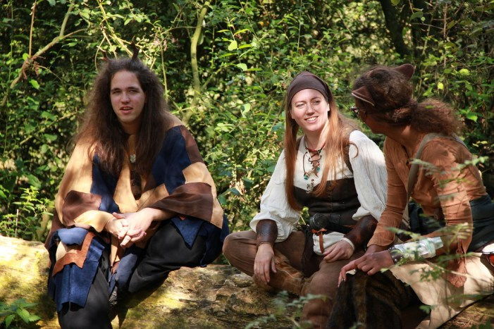 LARPers in conversation, seated on a log
