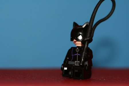 A small Cat Woman lego figure, brandishing a long black whip.
