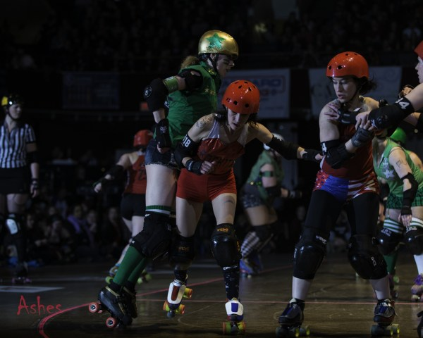 A small skater in red hits a larger skater in green with her hip while two other skaters in red prepare themselves to block. In the background are more skaters in green and a referee.