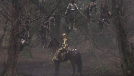 Mordred ontop a horse in a forest underneath bodies (clearly knights) hanging from tree limbs.