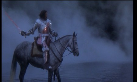 Perceval ontop a horse in armor wielding a bloody Excalibur on the Lake. There's mist and fog all behind him.