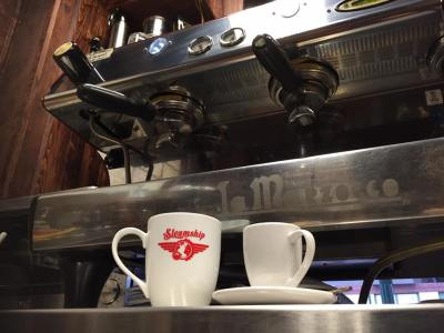 Two cups sit in front of an espresso machine at Steamship Coffee and Tea