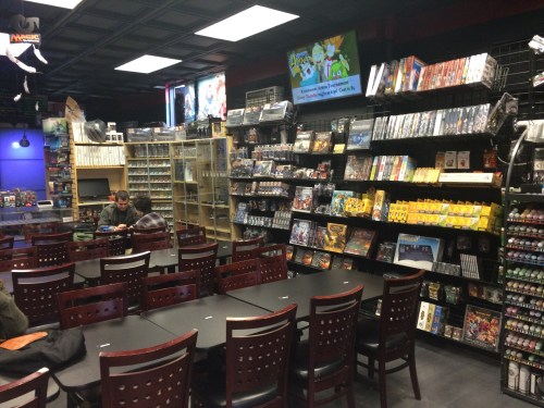 A view of the gaming space--shelves of games, tables, and chairs.