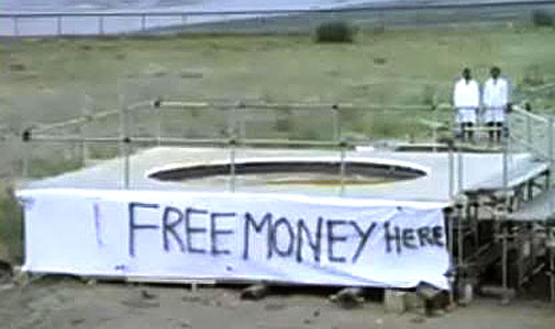 "The words ""FREE MONEY HERE"" spray painted on a platform in a field."