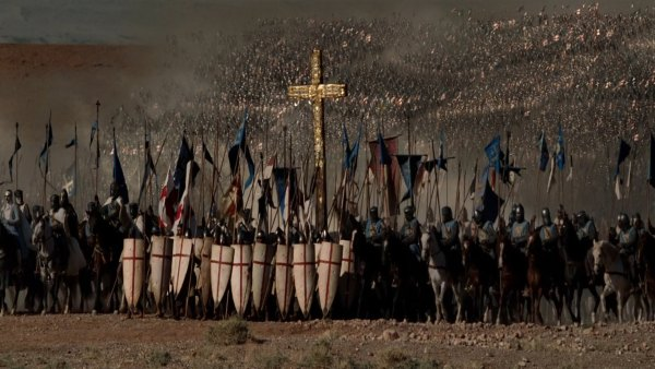 Christian Crusaders. A multitude of crusaders. At the forefront, there are some with the cross shields, a large cross and bannaers and people on horses.