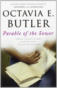 The book cover of Parable of the Sower. There is an image of hands with dark skin leafing through pages of a book. You cannot see who the hands belong to.
