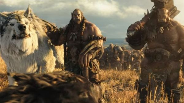 Warcraft movie still showing two orcs and a frostwolf in a grass field, with an army behind them