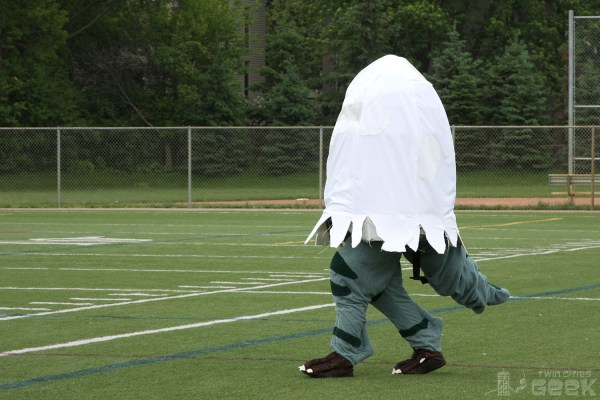 A human dressed in a hatching dino costume walks across a football field. The hatching egg portion of the costume covers the dino from the knees up, leaving only the legs and tail revealed.