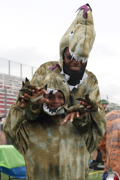 A mother and son, both dressed as T-Rexes, pose for the camera. The son is smiling and making T-Rex hands at the camera, while the mother smiles and looks down at her son.