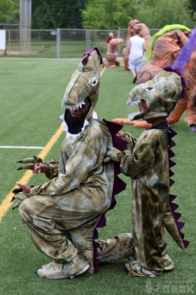A mother and son are dressed in T-Rex costumes. The mother kneels on the ground so that the son can adjust the scales on her back.