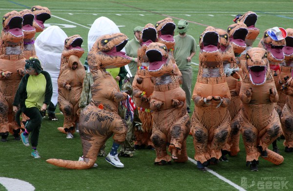 A group of humans in inflatable T-Rex costumes job side-by-side on a football field, some better than others.