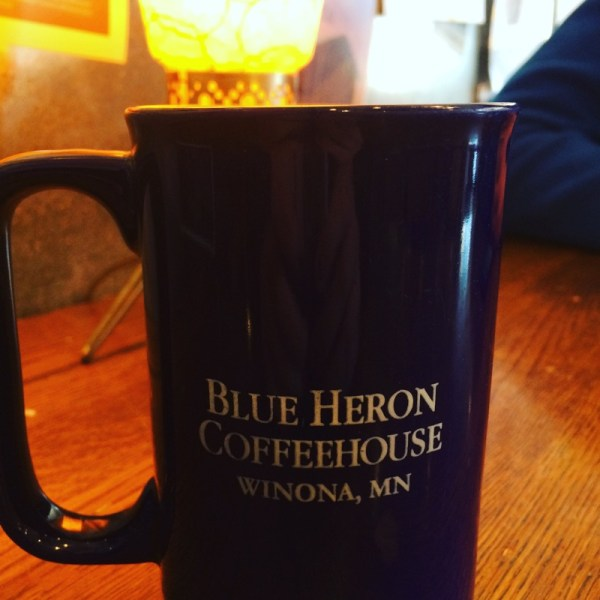 A mug with the words BLUE HERON COFFEEHOUSE and WINONA, MN