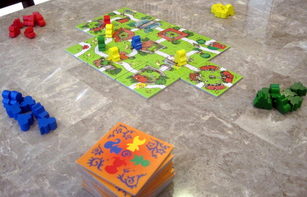 "A number of cards for the game are laid out, with ""meeple"" on the closed roads"