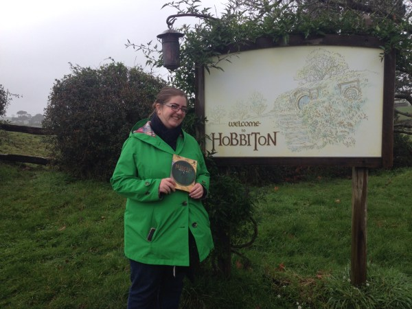 Katy at the entrance to Hobbiton, complete with signage and a map.