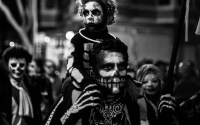 An adult man and child wearing calavera make up for the annual celebration of Dia de los Muertos in the Mission District of CA.