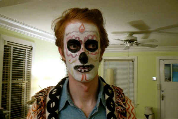 "A presumably white guy with red hair dressed in stereotypical ""Mexican"" clothing with poorly painted on sugar skull makeup."