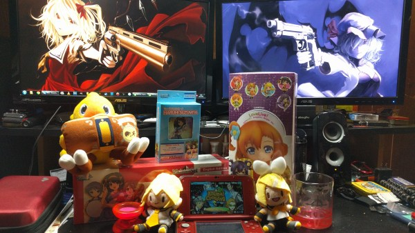 A small part of the author's anime merch collection and custom PC in the background.