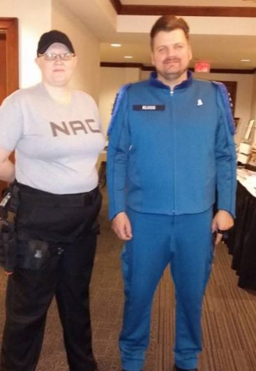 Man and woman standing in NAC uniforms
