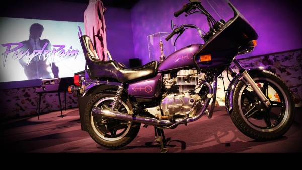 "A purple motorcycle with the ""male"" symbol on it in front of a screen showing scenes from the film Purple Rain"