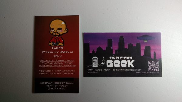 A pair of Tom Moen's business cards, with his personal geek card on the left with information to get in touch with him for cosplay repair and advertising his social media. On the right is Tom's Twin Cities Geek business card.