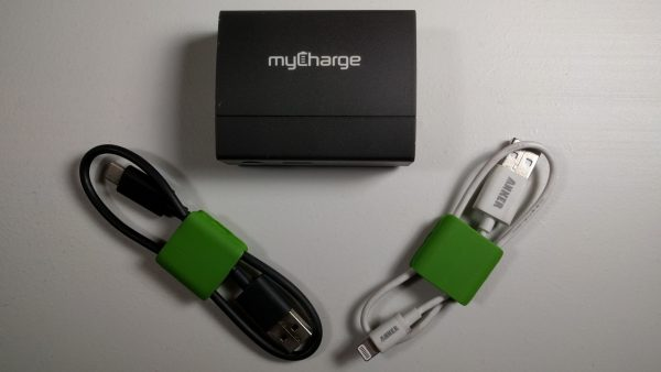 The image consists of a USB power bank used to wirelessly recharge mobile devices, with a USB-C cable and an Apple Lightning cable.