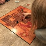 Tsuro in play. A child is laying a path tile and getting ready to move her token