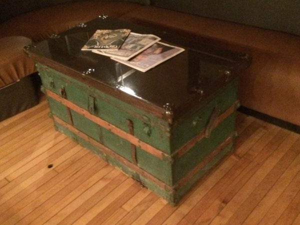 Green steamship trunk has been refurbished with a wood top and glass finish, to serve as a drinks table in Clockwerks Brewing.