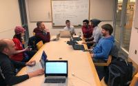 A group of coders sit around a table with their laptops and discuss code