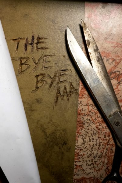 Rusty scissors next to the carved words THE BYE BYE MAN