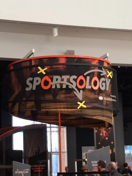 Sportsology sign. The two o's are colored and there are 3 Xs placed on the sign.