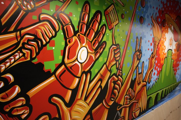 A mural featuring raised hands of various geeky types