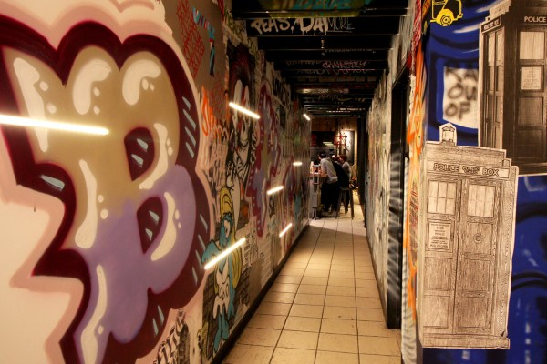 "A hallway featuring ""graffiti"" and other street-style art"