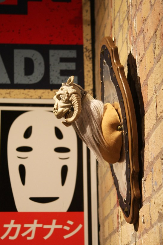A gargoyle bust on the wall in front of a No-Face poster