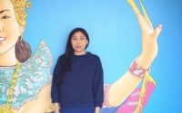 Saymoukda standing in front of a colorfully painted wall