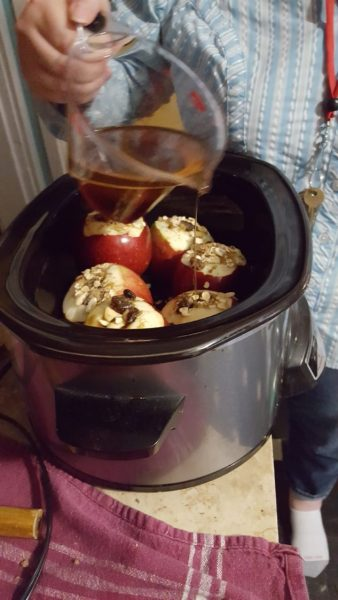 Pouring the glaze onto the stuffed apples in the slow cooker