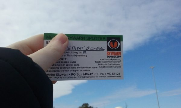 Hand holds up Metro Skywarn id in front of blue sky with cloud