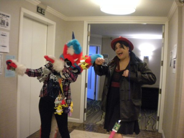 Twin Cities Geek contributor Becky Elfprincess dances with a con attendee wearing a colorful fursuit