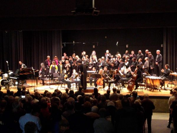 A choir of people of various races on a rather wide high school auditorium stage.