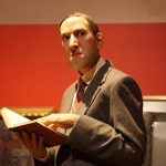 A wax model of H. P. Lovecraft holding a book