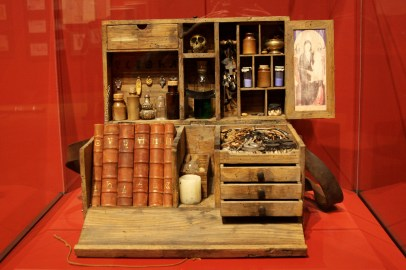 A box full of books, small vials, and other curios